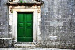 Alte grüne Holztür in der Backsteinmauer Stockfotos