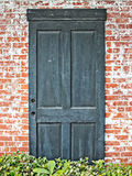 Alte grüne Tür in der Wand des roten Backsteins Stockfoto