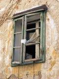 Alte grüne zerbrochene Fensterscheibe mit weißem Vorhang ein verlassenes Haus in Bakar, Kroatien Stockbild
