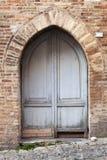 Alte graue Holztür mit Bogen in der Backsteinmauer Lizenzfreie Stockfotografie
