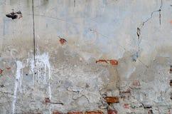 Alte graue konkrete Garagenwand mit Sprüngen und Stellen der roten Backsteine Lizenzfreie Stockfotos
