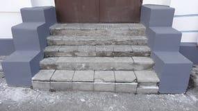 Alte graue Steinschritte mit Verschleißerscheinung der Zerstörung mit Kratzern und Sprüngen zur roten Tür auf der Straße Stockbild