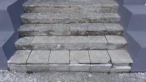 Alte graue Steinschritte mit Verschleißerscheinung der Zerstörung mit Kratzern und Sprüngen zur roten Tür auf der Straße Lizenzfreies Stockfoto
