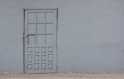 Alte graue Tür in der Betonmauer Lizenzfreies Stockbild