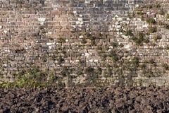 Alte große verwitterte Backsteinmauer Stockbilder