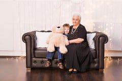 Alte Großmutter mit ihrem Enkel, der auf einem Sofa sitzt stockfotografie