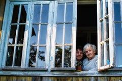 Alte Großmutter und ihre erwachsene Tochter auf dem Fenster des Dorfhauses hilfe stockfotografie