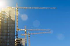 Alte gru sulla costruzione degli edifici residenziali, contro il cielo blu Fotografie Stock Libere da Diritti