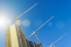 Alte gru sulla costruzione degli edifici residenziali, contro il cielo blu Fotografia Stock
