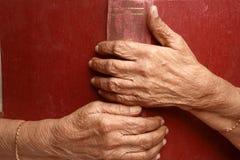 Alte Hände auf einem alten Buch Lizenzfreies Stockfoto