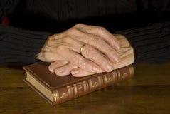 Alte Hände, die an der antiken Bibel stillstehen Lizenzfreies Stockfoto