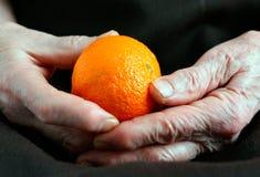 Alte Hände mit einer Orange auf einem schwarzen Hintergrund Stockbilder