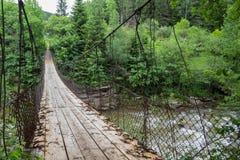Alte Hängebrücke über dem Fluss im Wald lizenzfreie stockbilder