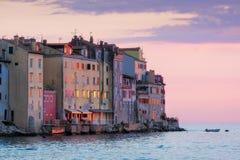 Alte Häuser in Ozean fahren bei buntem Sonnenuntergang in Rovinj, Kroatien die Küste entlang stockfotos