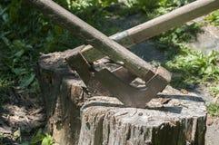 Alte hölzerne Äxte auf hölzernem Klotz Stockfotos