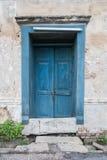 Alte hölzerne blaue Tür in der Wand des Altbaus Stockbild