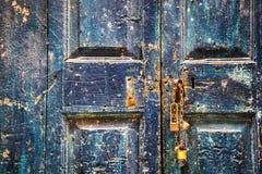 Alte hölzerne blaue Tür mit Vorhängeschlössern Lizenzfreie Stockbilder