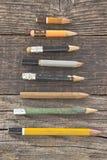 Alte hölzerne Bleistifte auf hölzernem Hintergrund Stockfotografie