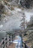 Alte hölzerne Bohlenbrücke und schöner See mit Nebelhintergrund Lizenzfreie Stockfotos