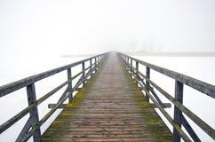 Alte hölzerne Brücke im Wintermorgennebel Stockfoto