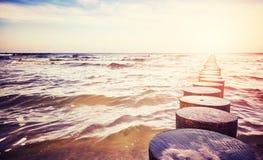 Alte hölzerne Buhne auf einem Strand Stockfoto