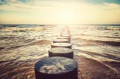 Alte hölzerne Buhne auf einem Strand Stockbilder