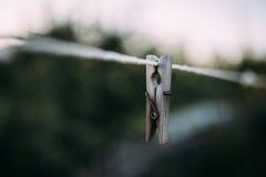 Alte hölzerne clothespegs, die am Seil hängen Lizenzfreie Stockfotografie