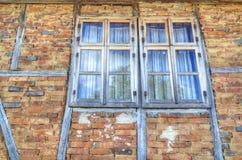 Alte hölzerne Fenster auf Backsteinmauer Stockbilder