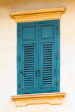 Alte hölzerne Fensterläden auf dem Fenster im Blau Lizenzfreie Stockfotos