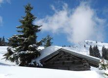 Hölzerne Gebirgshütte bedeckt durch Schnee - österreichische Alpen gestalten landschaftlich Lizenzfreies Stockbild