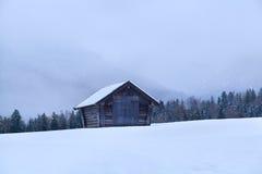 Alte hölzerne Hütte in der schneebedeckten Wiese in den Alpen Lizenzfreie Stockbilder