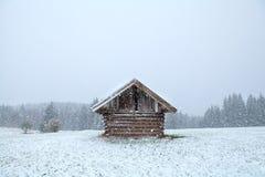 Alte hölzerne Hütte im Schneesturm Stockbilder