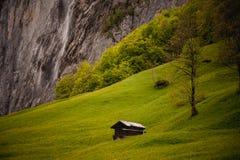 Alte hölzerne Hütte nahe dem Berg und dem Wasserfall Lizenzfreie Stockbilder