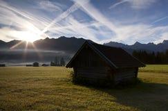 Alte hölzerne Hütte am Sonnenaufgang Stockbilder