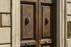 Alte hölzerne Haustür verziert mit zwei Löweköpfen Metall PA Stockfotos