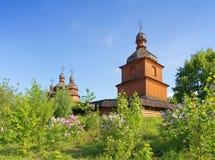Alte hölzerne Kirche und lila Bäume Stockbilder