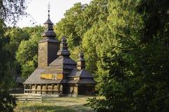 Alte hölzerne Kirche unter den Bäumen Lizenzfreie Stockfotografie