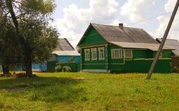 Alte hölzerne ländliche Häuser des Dorfs mit schrägem Dach neben der grünen grasartigen Lichtung, den Bäumen und der Straße Russl Stockbild