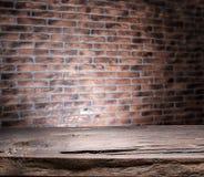 Alte hölzerne leere Tabelle und Backsteinmauer Lizenzfreie Stockbilder