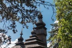 Alte hölzerne Lemk-Kirche gegen einen hellen blauen Himmel mit Wolken Stockfoto