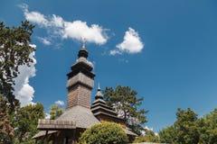 Alte hölzerne Lemk-Kirche gegen einen hellen blauen Himmel mit Wolken Stockfotografie