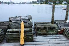 Alte hölzerne losbster Fallen gestapelt auf einem nassen hölzernen Dock an einem regnerischen Tag mit Bucht und Häusern im Abstan Stockfotos
