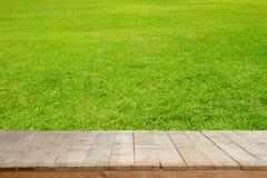 Alte hölzerne Planken oder Holztisch mit grünem Rasen für Hintergrund lizenzfreies stockfoto