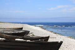 Alte hölzerne Ruderboote auf steiniger Seeküste Stockbilder