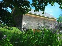 Alte hölzerne Scheune umrissen mit grünen Bäumen und purpurroten Blumen Lizenzfreie Stockfotos