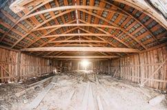 Alte hölzerne Scheune voll des alten Heus mit dem hellen Glänzen durch die hölzernen Bretter Stockbilder