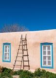 Alte hölzerne Strichleiter, die an der Ziegelsteinwand sich lehnt Lizenzfreie Stockfotografie