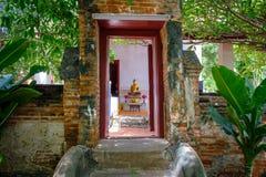 Alte hölzerne Tür auf Backsteinmauerarchitektur von schönem altem Buddha Stockfoto