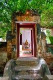 Alte hölzerne Tür auf Backsteinmauerarchitektur von schönem altem Buddha Stockfotos