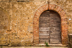 Alte hölzerne Tür und Backsteinmauer Stockbild